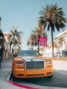orange car parked on sidewalk during daytime