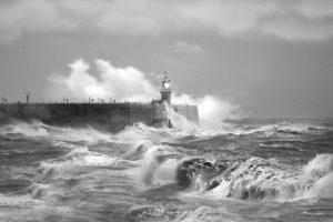 grayscale photo of sea waves crashing on concrete wall